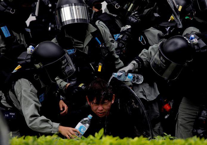 Oproerpolitie giet water in de ogen van een demonstrant die was bestookt met traangas. Het is al tijden onrustig in Hongkong.