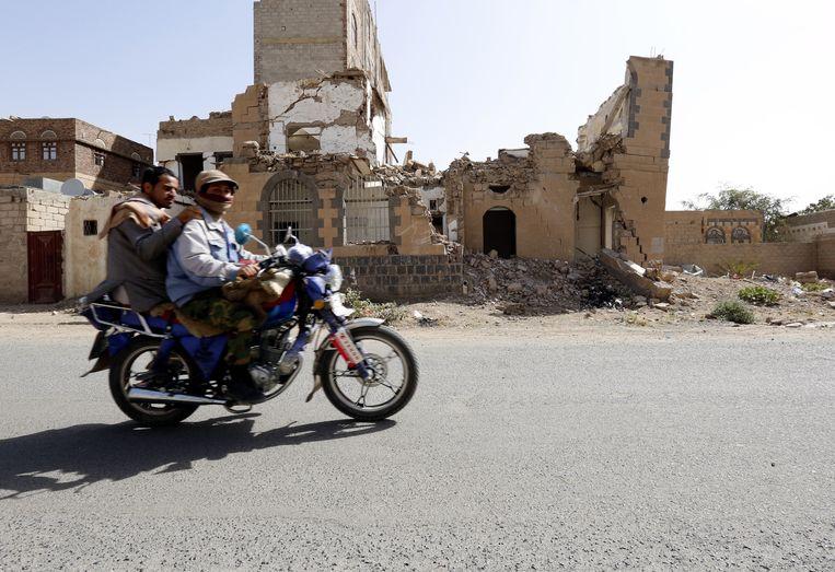 Twee mannen rijden op een motorfiets door de Jemenitische hoofdstad Sanaa. Ze rijden langs een gebouw dat geraakt is tijdens een luchtaanval die vermoedelijk werd uitgevoerd door de Saudi's. Beeld EPA