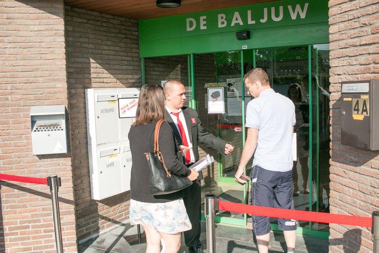 Een veiligheidsagent deelt nummertjes uit aan de toegang van het gebouw van de FOD Financiën aan Driekoningen, waar het de voorbije weken vaak heel druk was.