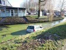 Man en vrouw in auto te water in Beesd