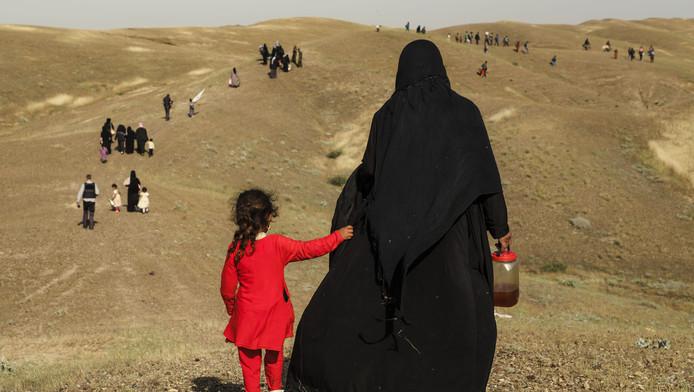 Een Irakese vluchtelinge loopt na bomaanslagen met haar dochter door de woestijn op zoek naar veiligheid in Noord-Kurdistan in Irak, 2016.