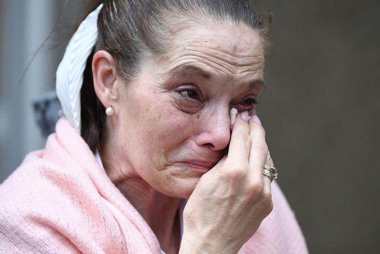 Een van de vrouwen die Johnson & Johnson had aangeklaagd, huilt na de uitspraak buiten de rechtbank in Sydney. Beeld EPA