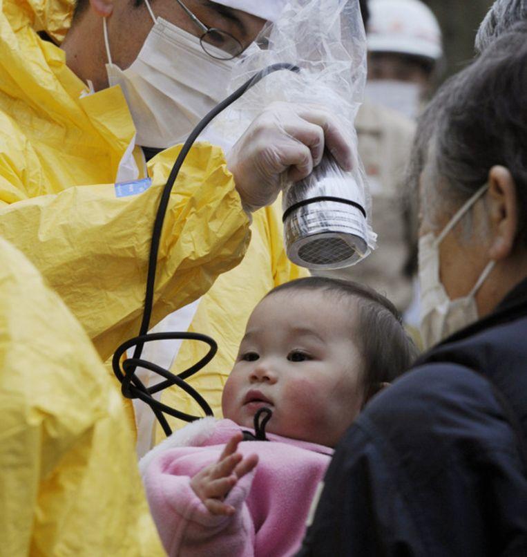 Een baby wordt gecontroleerd op straling in Nihonmatsu. Beeld ap