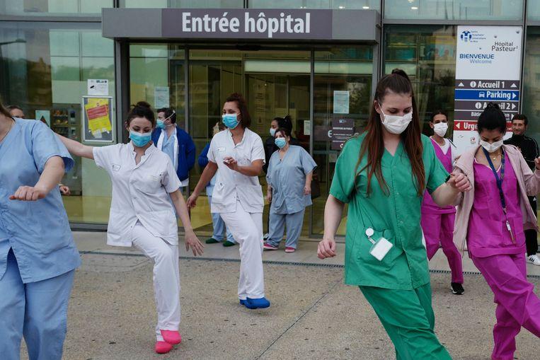 Medische staf van het Pasteur Universitair Ziekenhuis danst voor het ziekenhuis als onderdeel van een dagelijks eerbetoon aan zorgmedewerkers. Beeld AFP