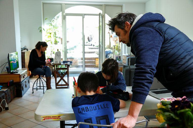 In België geeft vader Joel Kockaert huiswerkbegeleiding aan zijn zoon.   Beeld REUTERS