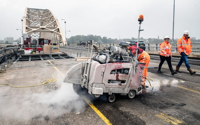 Met een enorme zaagmachine wordt oud beton van de Waalbrug in Nijmegen in stukken gezaagd.