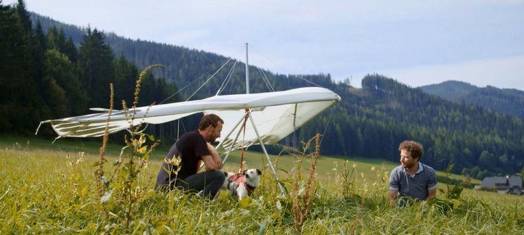 Johannes Hogebrink (links) leert hetn hondje Chayka vliegen met een deltavleugel. Beeld