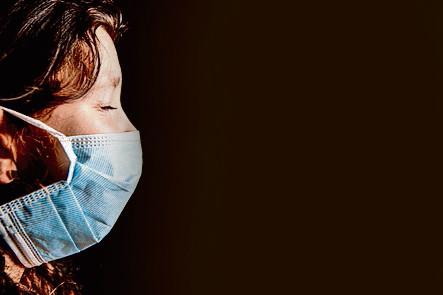 Vrouw en kind met met mondkapjes op ter bescherming van het coronavirus .
