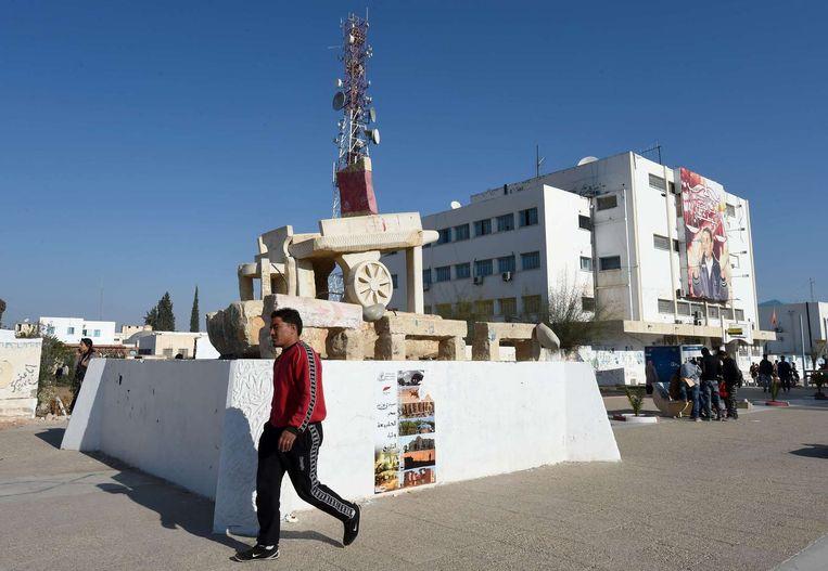 Een man loopt langs een monument dat armoede moet verbeelden. Het is een handkar zoals Mohamed Bouazizi ook had, om zijn groenten op te verkopen. Beeld null