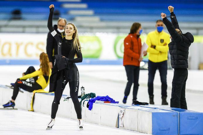 Jutta Leerdam juicht samen met coach Kosta Poltavets (rechts) na het winnen van de 1000 meter tijdens de NK Afstanden.