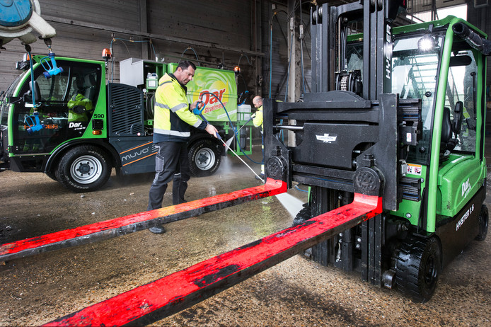 Patrick van Blijderveen, medewerker van de reinigingsdienst Dar, spuit de nieuwe heftruck in NEC-kleuren schoon. Foto: Bert Beelen