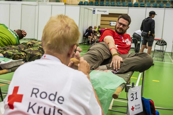 Vrijwilligers van het Rode Kruis behandelen wandelaars tijdens de tweede dag van de 103e editie van de Nijmeegse Vierdaagse.