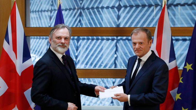 Britse vertegenwoordiger bij de EU, Tim Barrow (links), overhandigt de Brexit-brief aan EU President Donald Tusk Beeld reuters