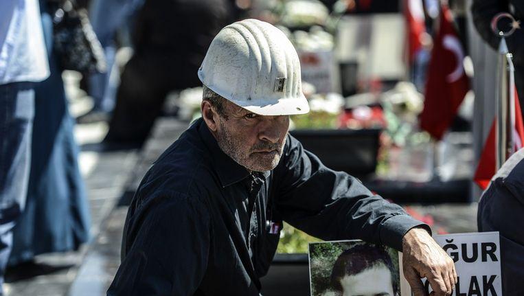 Een man bij het graf van een omgekomen mijnwerker tijdens een herdenking van de mijnramp in Soma. Vorig jaar kwamen toen 301 mensen om het leven. Beeld afp