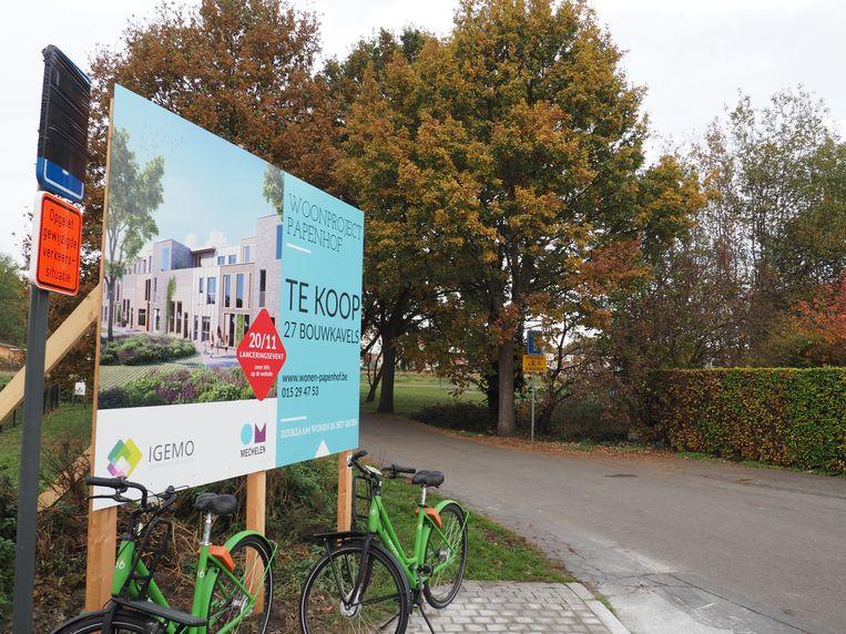 Een bord aan de Papenhofdreef kondigt de verkoop van de kavels op Papenhof aan. De nieuwe woningen komen op het grasland achter de bomen op de foto.