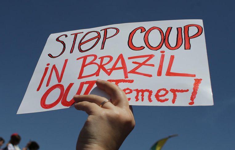 Een demonstrant houdt een bord omhoog tijdens protesten in de hoofdstad Brasilia. Beeld ap