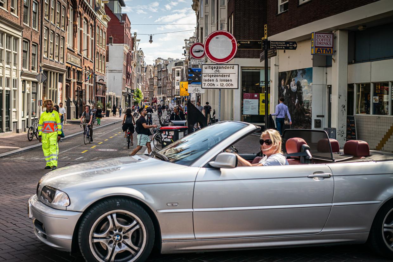 Handhavers houden mensen tegen die toch de Haarlemmerstraat in willen rijden. Beeld Joris Van Gennip