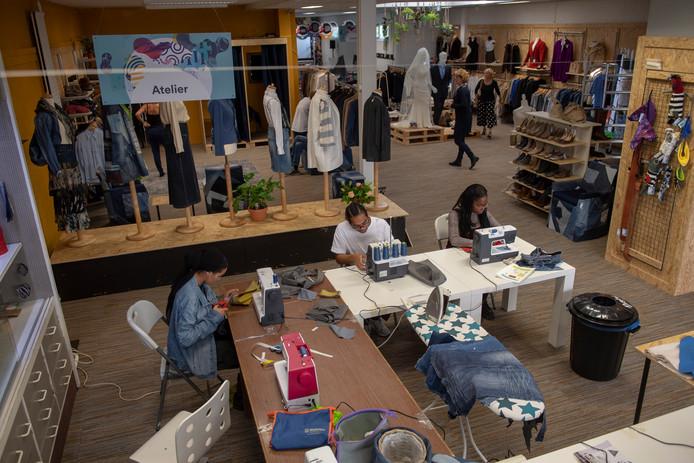 De tijdelijke winkel 013Circles in Tilburg. ROC-studenten Ahlem, Santana en Jo-Amy zitten achter de naaimachine.