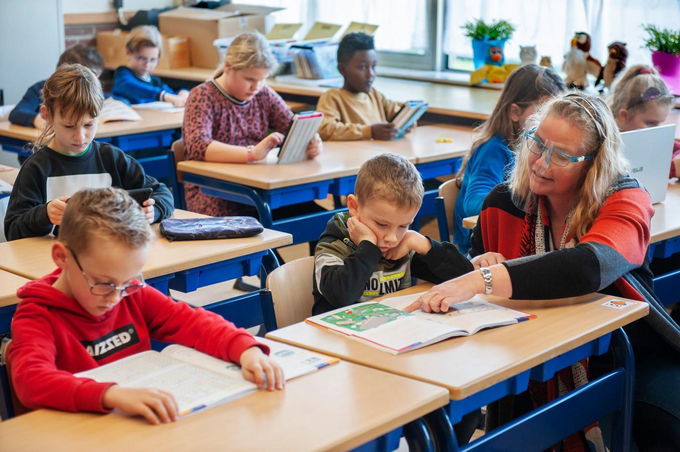 Kinderopvang tijdens de lockdown bij basisschool De Duinsprong in Drunen. Juf Joriza geeft ondersteuning bij het zelfstandig werken van de leerlingen.