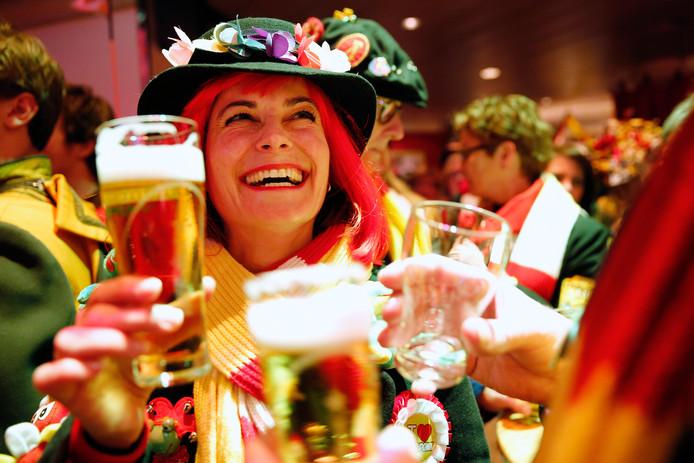 Foto ter illustratie. Een vrouw drinkt bier op carnavalsdinsdag in een druk café.