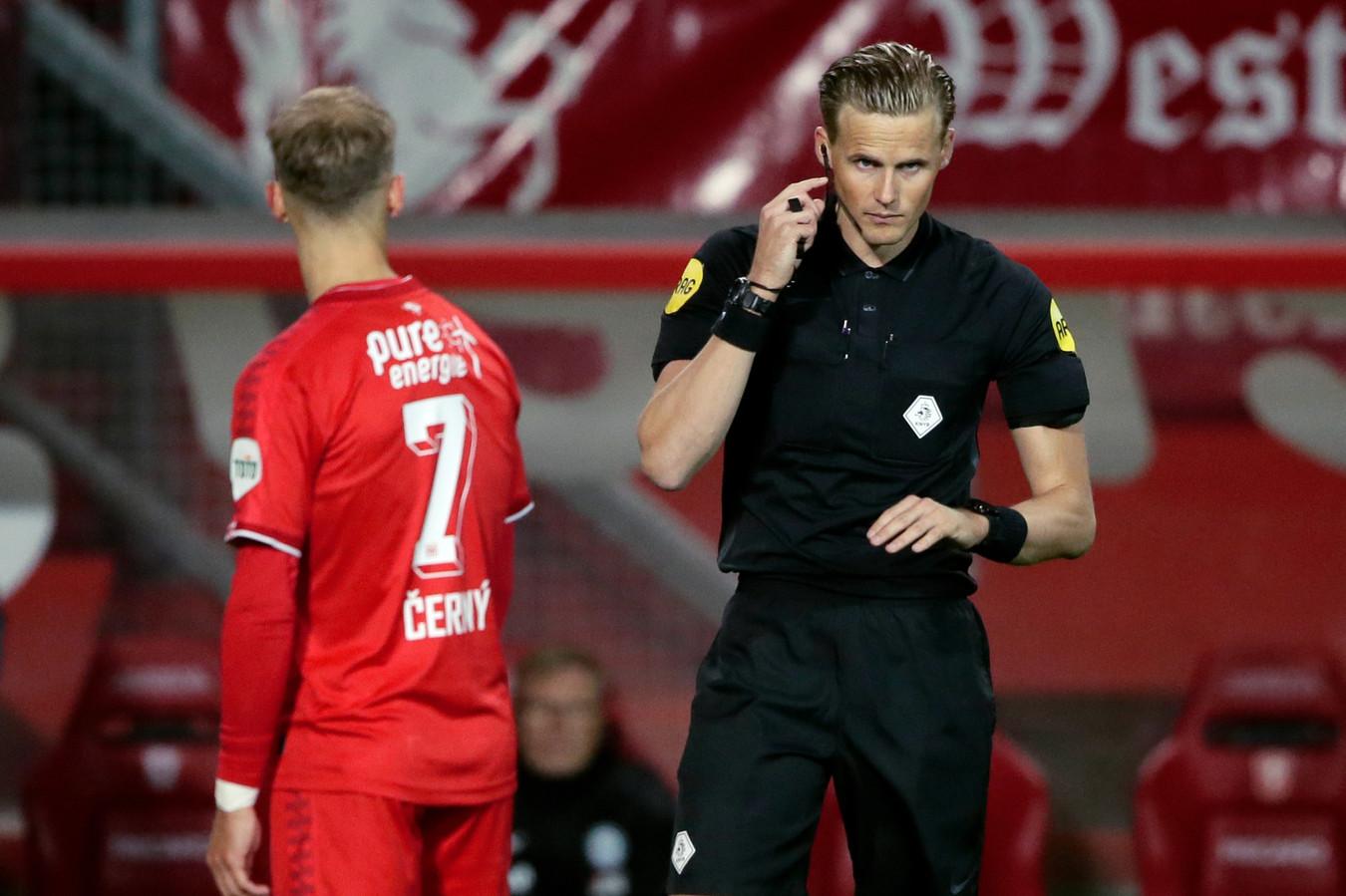 Referee Sander van der Eijk heeft contact met de VAR, terwijl de doelpuntenmaker Vaclav Cerny wacht en toekijkt.