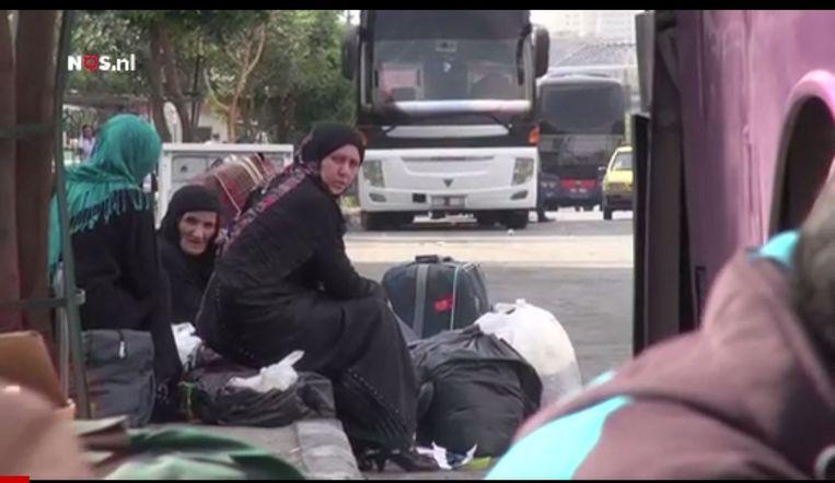 Reizigers wachten op de bus van Damascus naar Raqqa. Beeld NOS