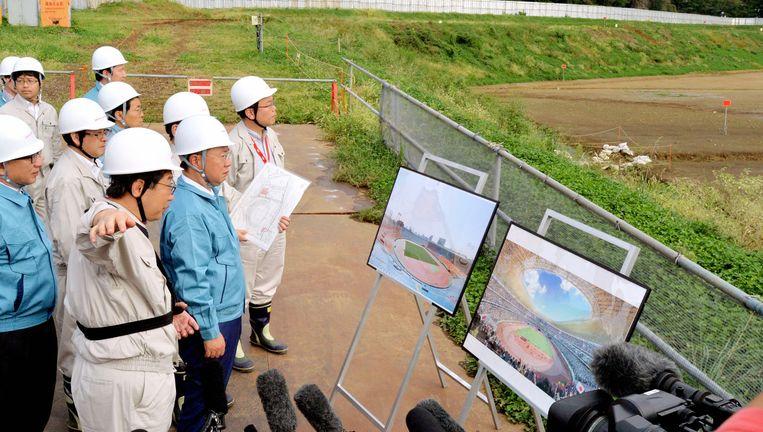 Japanse officials inspecteren de plannen voor het olympisch stadion voor de Spelen van 2020. Beeld The Asahi Shimbun via Getty Imag