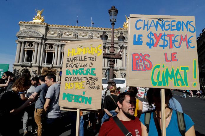 """Protestborden met de tekst: """"Mensen herinner u waar we vandaan komen! De natuur is sinds ons bestaan ons grootste medicijn"""" en """"Verander het systeem, niet het klimaat""""."""