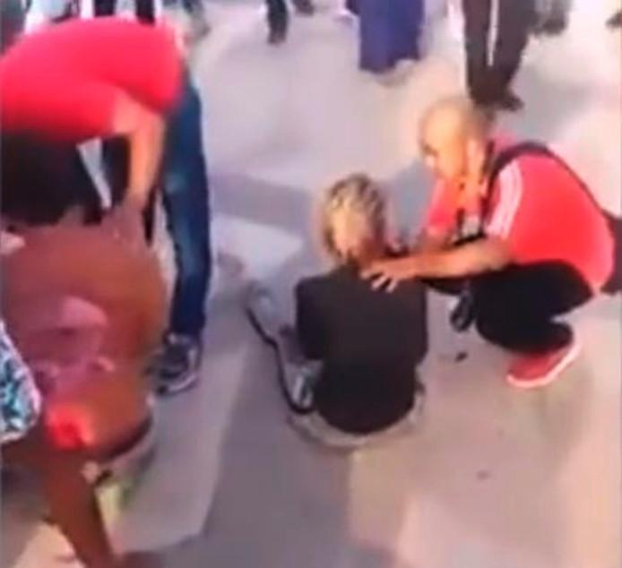 Een omstander helpt een van de neergestoken Vughtenaren.