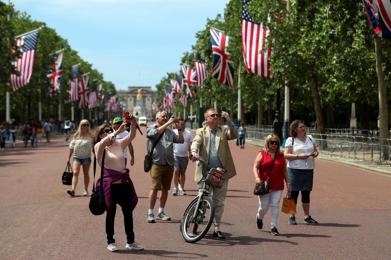 Toeristen maken foto's van Amerikaanse vlaggen aan The Mall, de weg die leidt naar Buckingham Palace.  Beeld Reuters