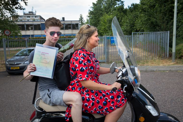 18 juli 2018. Toch geslaagd: een leerling laat, achter op de scooter bij zijn moeder, zijn diploma zien. Beeld Arie Kievit
