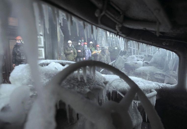 Zicht op betogers vanuit een door brand verwoeste, met ijs bedekte auto. Beeld reuters
