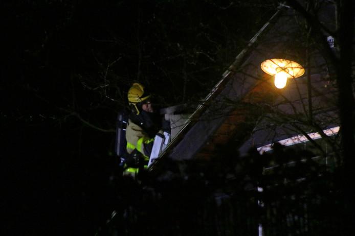 Een brandweerman inspecteert de schoorsteen van Huisje James.