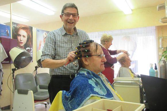 Walter legt de laatste krullen in deze vrouw haar haar.