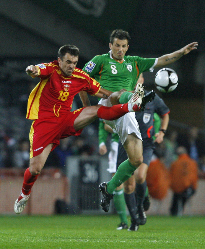 Liam Miller (r) namens Ierland in duel met de Montenegrijn Nikola Drincic op 14 oktober 2009.