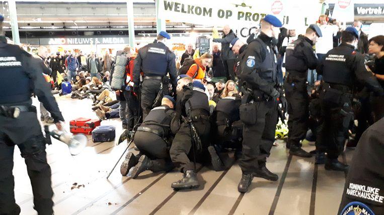 De Marechaussee begint met de ontruiming van de centrale hal van Schiphol. Beeld Het Parool