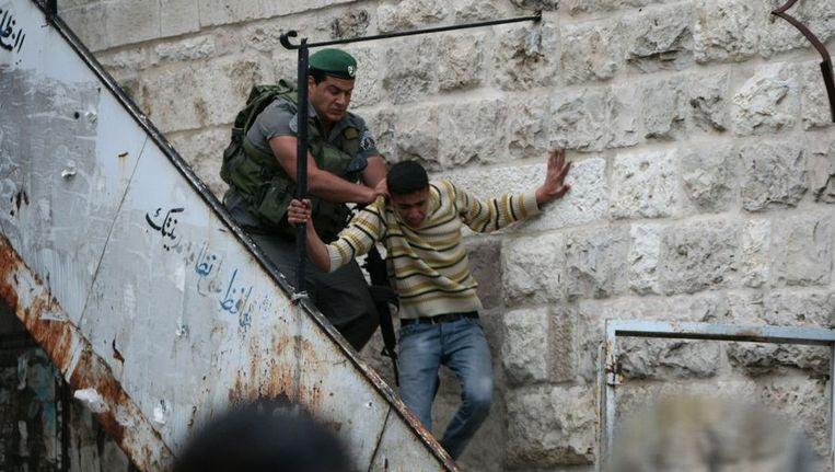 Een Israëlische soldaat verwijdert een Palestijnse betoger in Hebron, op 1 april. Beeld AFP