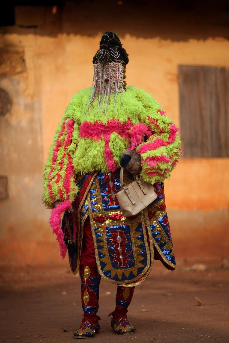 Een Egungun, een gemaskerde danser uit Quidah (Benin) tijdens een voodooceremonie. Beeld Getty Images