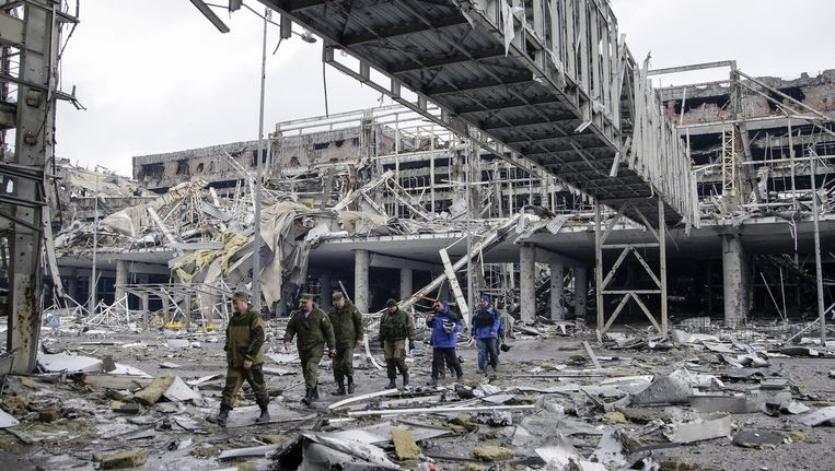 Pro-Russische separatisten leiden OVSE-waarnemers rond op het verwoeste vliegveld van Donetsk Beeld epa