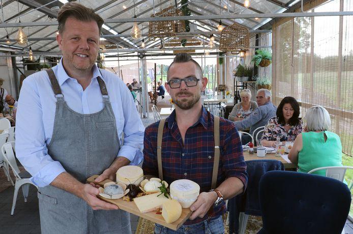 Gert Laurijssen en Yanniek Perron met een plankje met daarop alle kazen van De Lochtenberg in Merksplas.
