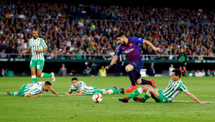 Luis Suárez laat de defensie van Real Betis verslagen op de grond achter en maakt 0-3.