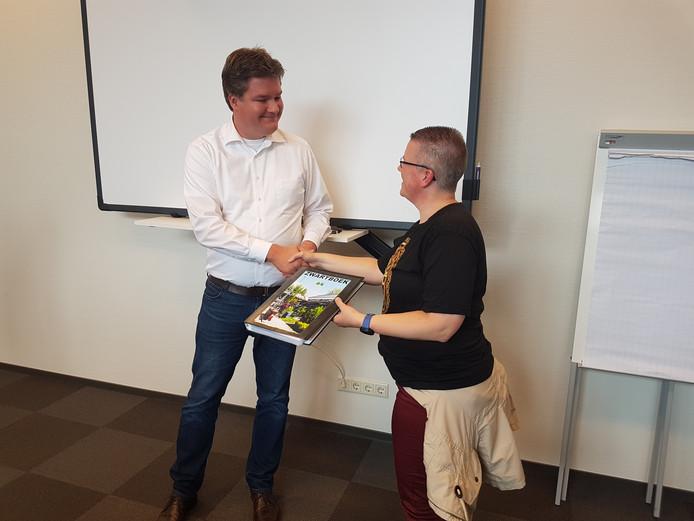 Woonconsulent Henk Kos neemt het zwartboek in ontvangst uit de handen van Anneke Popa.