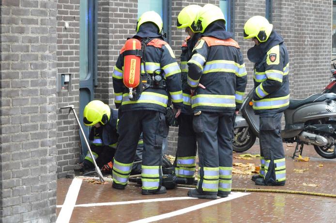 Brandweerlieden hebben de buitenmuur opengebroken om bij de brand te komen.
