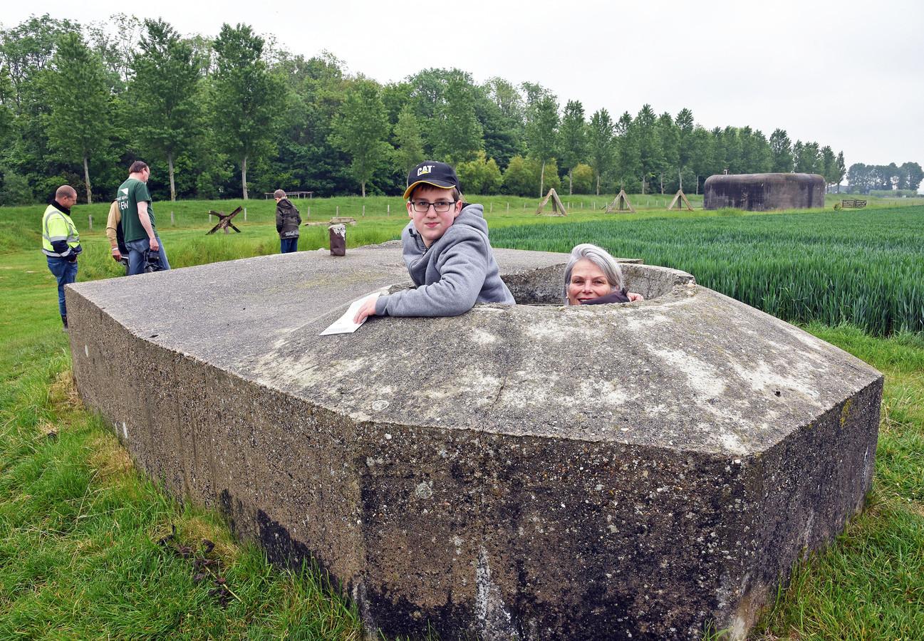 Ilian van Duren en Monique van der Peijl steken hun hoofd door een geschutskoepel.
