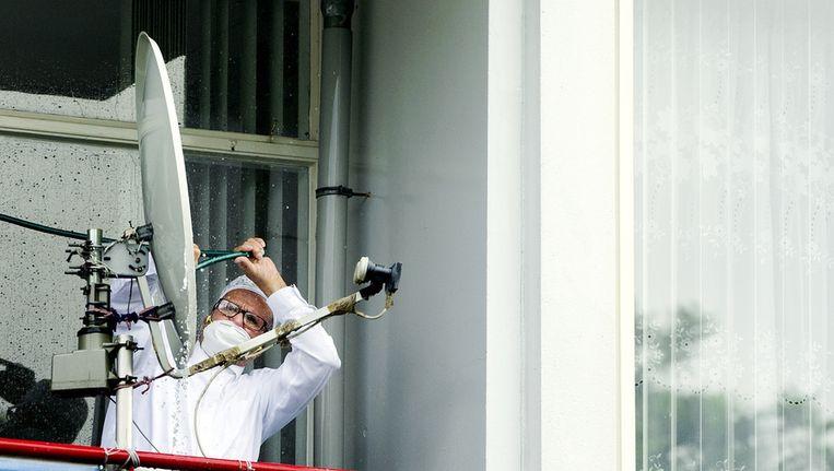 Een bewoner van de met asbest besmette flat aan de Marco Pololaan in de Utrechtse wijk Kanaleneiland spuit zijn schotelantenne schoon na terugkomst. Beeld ANP