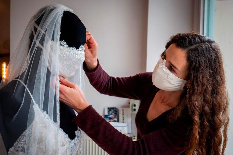 Modeontwerper Friederike Jorzig plaatst een bruidsmondkapje op een mannequin in haar winkel in Berlijn.  Beeld AFP