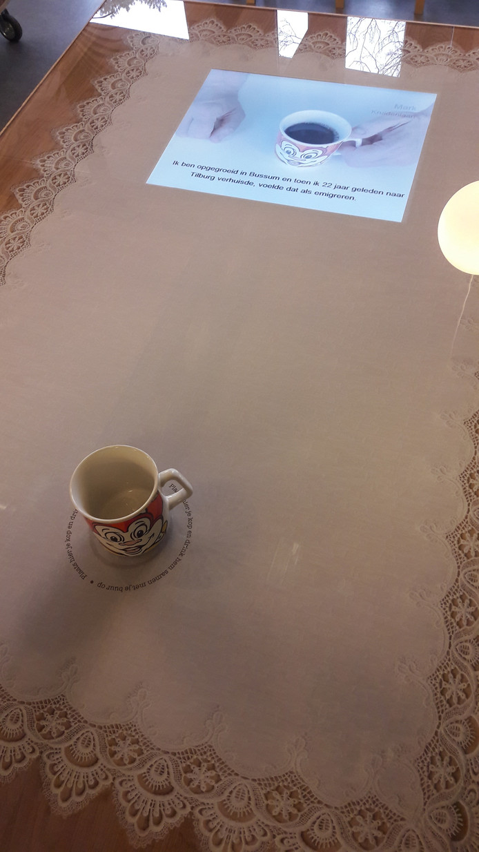 Als het kopje op de tafel wordt gezet, verschijnt het bijbehorende verhaal in het scherm.