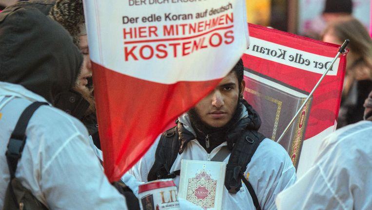 Een aanhanger van Die Wahre Religion deelt gratis Duitse Korans uit. Beeld AFP