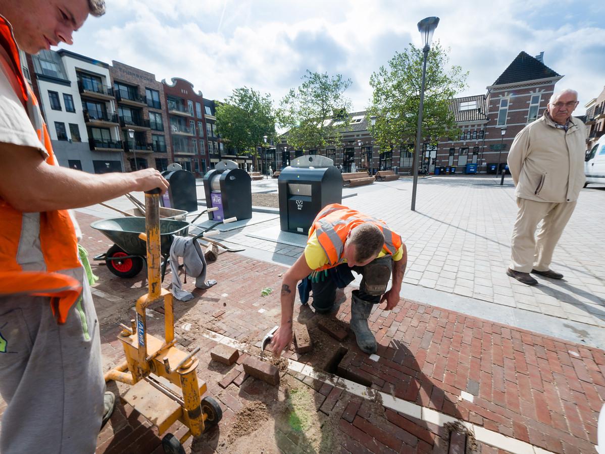 Stratenmakers Kevin Blom (m) en Sander Kolderman werken onder toeziend oog van een passant aan de laatste opleverpunten op het Thorbeckeplein in Alphen.