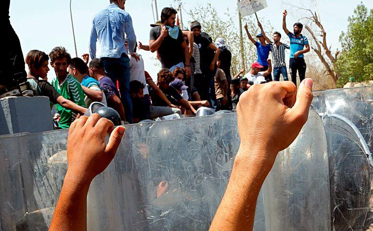 De Iraakse oproerpolitie belet demonstranten een overheidsgebouw te bestormen in de zuidelijke stad Basra. Beeld AP
